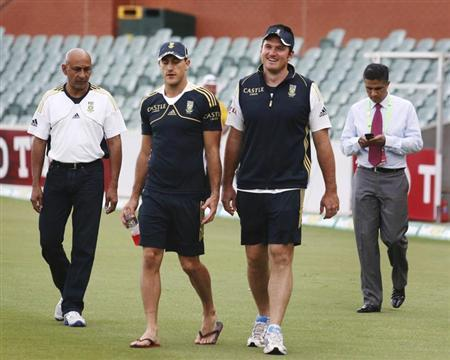South Africa's captain Graeme Smith (centre R) walks with teammate and player of the match Faf du Plessis (centre L) onto the Adelaide cricket ground after the fifth day's play of the second test cricket match against Australia November 26, 2012. REUTERS/Regi Varghese/Files