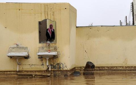 A Saudi man is reflected in a mirror in his flooded home after heavy rain in Tabuk, Saudi Arabia, January 28, 2013. REUTERS/Mohamed Alhwaity