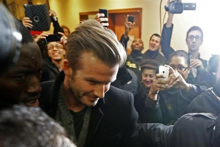 People take photos of soccer player David Beckham (C), surrounded by body guards, at the Pitie-Salpetriere hospital after his medical examination in Paris January 31, 2013. REUTERS/Charles Platiau