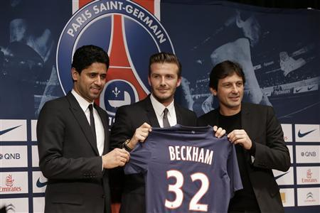 Soccer player David Beckham (C) poses with his new jersey at a news conference in Paris January 31, 2013. Former England captain Beckham has joined Paris St Germain on a five-month contract, the French Ligue 1 club said on Thursday. Beckham poses with Nasser Al-Khelaifi (L), Paris St Germain's club owner and owner of Qatari TV channel Al Jazeera Sport, and President of beIN Sport French TV channel and Paris St-Germain sports director Leonardo (L). REUTERS/Philippe Wojazer
