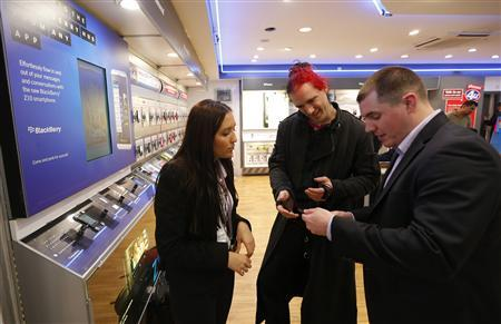 Ben Stephens (R), a Blackberry sales manager demonstrates a new Blackberry Z10 to prospective customer Shevek (C), as store manager Alejandra Escobar watches at a branch of UK retailer Phones 4U in central London, January 31, 2013. Blackberry's new Z10 model went on sale in the UK today. Research In Motion Ltd's glitzy unveiling of the long-delayed line of BlackBerry smartphones on Wednesday and a new corporate name failed to impress Wall Street analysts, with at least three downgrading the company's stock. REUTERS/Andrew Winning