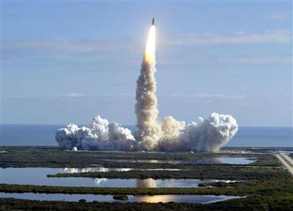The space shuttle Columbia lifts off from the Kennedy Space Center in Cape Canaveral, Florida, reflected in salt marsh swamps surrounding the pad in this file photo from January 16, 2003. February 1, 2013 marks the 10th anniversary since the orbiter broke apart in the skies over Texas, killing the crew of seven astronauts. Columbia broke up as it re-entered the atmosphere because of damage to the leading edge of the left wing. REUTERS/Pierre DuCharme/Files