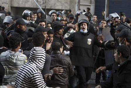 Riot police move in to detain anti-Mursi protesters during clashes in Simon Bolivar Square, which leads to Tahrir Square, in Cairo, January 30, 2013. REUTERS/Mohamed Abd El Ghany