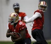 San Francisco 49ers quarterback Colin Kaepernick (R) hands off to running back Frank Gore (L) during practice for the Super Bowl in New Orleans, January 30, 2013. Super Bowl XLVII will be played between the San Francisco 49ers and the Baltimore Ravens on February 3. REUTERS/Jeff Haynes