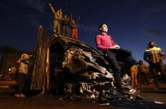 Protesters opposing Egyptian President Mohamed Mursi surround a burnt riot police vehicle after protesters seized it from the Qasr al-Nile bridge during previous clashes with riot police at Tahrir Square in Cairo January 31, 2013. Opponents of Mursi have called mass demonstrations on Friday, raising the prospect of more bloodshed despite a pledge by politicians to back off after the deadliest week of his seven months in office. REUTERS/Amr Abdallah Dalsh