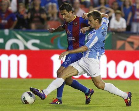 Malaga's Nacho Monreal (R) and Levante's Javi Venta fight for the ball during their Spanish first division soccer match at the Ciudad de Valencia Stadium in Valencia October 16, 2011. REUTERS/Heino Kalis