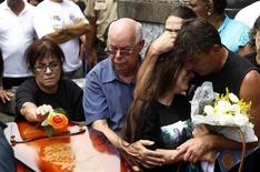 Maria Cristina Dias de Mattos (L), the mother of military doctor Daniele Dias de Mattos, a victim of the fire at Boate Kiss nightclub, places a flower over her coffin as her granddaughter Anna Carolina is comforted by a relative during the funeral at a local cemetery in Rio de Janeiro, January 30, 2013. REUTERS/Pilar Olivares