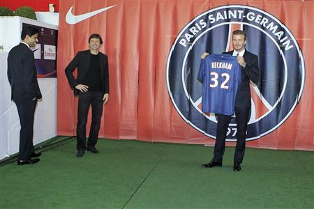 Soccer player David Beckham (R) presents his new jersey as he stands near Nasser Al-Khelaifi (L), Paris St Germain's club owner and owner of Qatari TV channel Al Jazeera Sport, President of beIN Sport French TV channel, and Paris St-Germain sports director Leonardo (C) after a news conference in Paris January 31, 2013. Former England captain Beckham has joined Paris St Germain on a five-month contract, the French Ligue 1 club said on Thursday. REUTERS/Gonzalo Fuentes