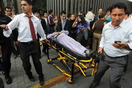 An injured person is transported on a stretcher the headquarters of state oil giant Pemex in Mexico City January 31, 2013. An explosion rocked the Mexico City headquarters of Pemex on Thursday, killing one person, injuring more than 20 others and causing extensive damage to the building. A local emergency official said one person had died in the blast and 22 others were injured. Another four people were trapped inside the skyscraper, the official said. The blast, which media reports said was caused by machinery exploding, occurred in the basement, emergency officials said. REUTERS/Alejandro Dias