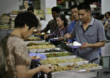People line up for free meals during lunchtime at the Singapore Buddhist Lodge June 6, 2008. REUTERS/Tim Chong/Files