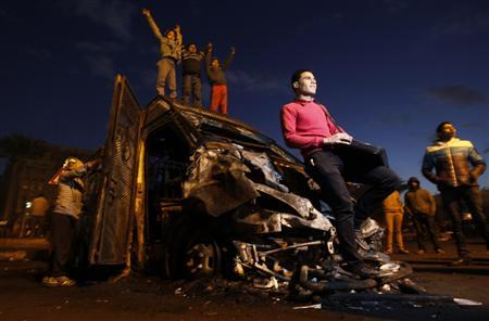 Protesters opposing Egyptian President Mohamed Mursi surround a burnt riot police vehicle after protesters seized it from the Qasr al-Nile bridge during previous clashes with riot police at Tahrir Square in Cairo January 31, 2013. REUTERS/Amr Abdallah Dalsh