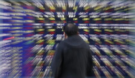 A man looks at a stock index board outside a brokerage in Tokyo January 30, 2013. REUTERS/Toru Hanai