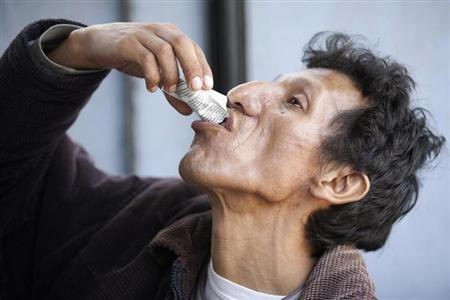 Eloy Pacheco, a tuberculosis patient, ingests a medicine from a free treatment at a medical post in the outskirts of Lima November 10, 2011. REUTERS/Enrique Castro-Mendivil/Files
