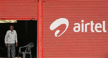 A man stands next to a shop painted with an advertisement for Bharti Airtel on the outskirts of Jammu December 11, 2012. REUTERS/Mukesh Gupta
