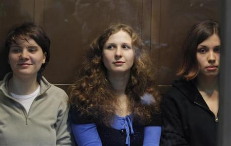 Members of the female punk band ''Pussy Riot'' (L-R) Yekaterina Samutsevich, Maria Alyokhina and Nadezhda Tolokonnikova sit in a glass-walled cage before a court hearing in Moscow October 10, 2012. REUTERS/Maxim Shemetov/Files