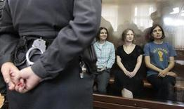 "Members of the female punk band ""Pussy Riot"" (R-L) Nadezhda Tolokonnikova, Maria Alyokhina and Yekaterina Samutsevich sit in a glass-walled cage during a court hearing in Moscow, August 17, 2012. REUTERS/Sergei Karpukhin"