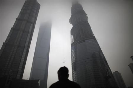 A man watches a construction crane lift a piece of steel at the Shanghai Tower (R) at the financial district of Pudong in Shanghai January 21, 2013. China's recovery from its longest slowdown in growth since the global financial crisis is being driven by the two forces posing the biggest risks to the economy's increasingly urgent need to rebalance - investment and property. REUTERS/Carlos Barria (CHINA - Tags: BUSINESS CONSTRUCTION)