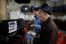 Инвестор следит за рыночными котировками в брокерской конторе в Шанхае 4 января 2013 года. Азиатские фондовые рынки завершили торги пятницы разнонаправленно после публикации отчета о производственной активности Китая. REUTERS/Aly Song