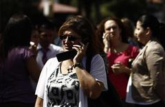Una donna parla al telefonino dopo essere srara evacuata. REUTERS/Juan Carlos Ulate