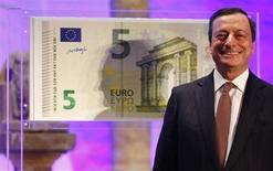 """Президент ЕЦБ Марио Драги улыбается на презентации новой купюры 5 евро во Франкфурте-на-Майне 10 января 2013 года. Международное рейтинговое агентство Standard and Poor's подтвердило в четверг высший рейтинг Европейского центробанка """"ААА"""", сославшись на кредитно-денежную гибкость банка и в среднем высокие суверенные рейтинги стран-членов еврозоны. REUTERS/Kai Pfaffenbach"""