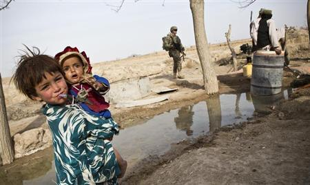 Afghan children are seen as soldiers from the U.S. Army's Bravo Company, 1st Battalion, 36th Infantry Regiment go on patrol near Command Outpost AJK (short for Azim-Jan-Kariz, a near-by village) in Maiwand District, Kandahar Province, Afghanistan, January 31, 2013. REUTERS/Andrew Burton