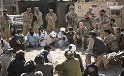 Afghans listen to a speaker at a shura - a meeting between village elders, U.S. troops and Afghan National Security Forces - near Command Outpost AJK (short for Azim-Jan-Kariz, a near-by village) in Maiwand District, Kandahar Province, Afghanistan, January 26, 2013. REUTERS/Andrew Burton