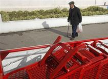 A man walks past supermarket carts that are lined outside, in Lisbon January 30, 2013. REUTERS/Jose Manuel Ribeiro