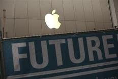 The Apple logo is pictured on the front of the company's flagship retail store near signs for the central subway project in San Francisco, California January 23, 2013.