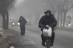 Pekín, que cuenta con una densa contaminación, pidió el viernes a sus habitantes que lancen menos fuegos artificiales en las celebraciones del Año Nuevo chino de este mes, en un momento en el que lucha contra una persistente crisis sobre la calidad del aire. En la imagen, un hombre se cubre la boca con una bufanda mientras conduce su bicicleta eléctrica en Pekín, el 22 d eneero de 2013. REUTERS/Jason Lee