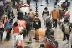 A paramilitary policeman (C) stands guard as passengers walk to board their trains at the Beijing West Railway Station January 31, 2013. REUTERS/Suzie Wong