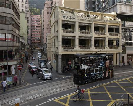 A man rides a bicycle next to a tram passing by a Chinese pawn shop that has been restored and partially converted into a restaurant at Hong Kong's Wanchai district February 1,2013. REUTERS/Tyrone Siu