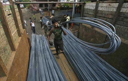 Labourers load iron rods onto a vehicle at a steel factory on the outskirts of Agartala November 1, 2012. REUTERS/Jayanta Dey/Files