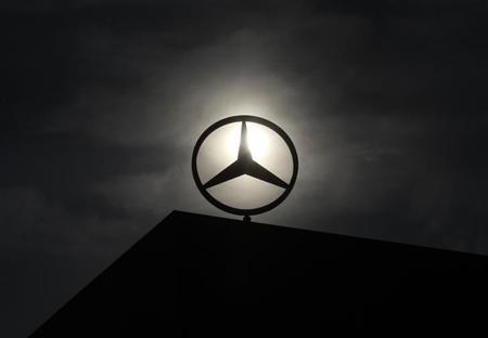 The logo of Mercedes Benz is seen on top of a car factory