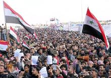 Sunni Muslims wave an old flag of Iraq (R) during an anti-government demonstration in Ramadi, 100 km (62 miles) west of Baghdad, February 1, 2013. REUTERS/Ali al-Mashhadani (