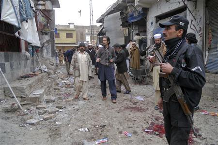 Police and members of the media gather at the site of a suicide bomb attack in the northwestern town of Hangu February 1, 2013. REUTERS/Syed Gilani