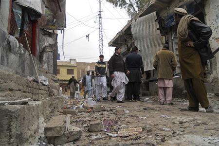 Residents gather at the site of a suicide bomb attack in the northwestern town of Hangu February 1, 2013. REUTERS/Syed Gilani