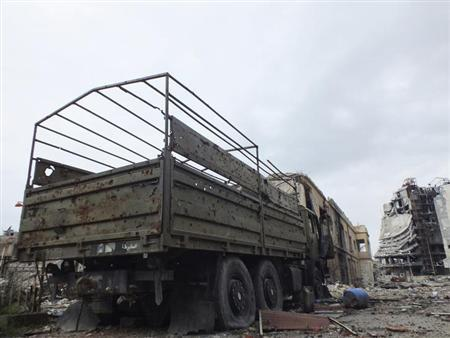 A damaged military vehicle that belonged to forces loyal to Syria's President Bashar al-Assad is seen in a damaged neighbourhood in Homs January 30, 2013. Picture taken January 30, 2013. REUTERS/Yazan Homsy (SYRIA - Tags: CONFLICT POLITICS CIVIL UNREST MILITARY)