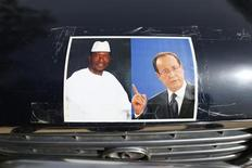 Photos du président malien par intérim Dioncounda Traoré et de François Hollande sur une voiture dans le centre de Tombouctou. Le chef de l'Etat se rendra samedi au Mali pour y rencontrer son homologue malien et saluer les troupes françaises engagées aux côtés de l'armée malienne pour déloger les rebelles islamistes du nord du pays. /Photo prise le 1er février 2013/REUTERS/Benoît Tessier