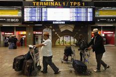 Passageiros carregam bagagem pelo terminal 1 do aeroporto internacional de Guarulhos, em São Paulo, em fevereiro de 2012. A Agência Nacional de Aviação Civil afirmou que iniciou audiência pública sobre regras mais duras para a utilização de espaços para pousos e decolagens (slots) em aeroportos que operam no limite da capacidade ou de grande importância nacional. 07/02/2012 REUTERS/Nacho Doce
