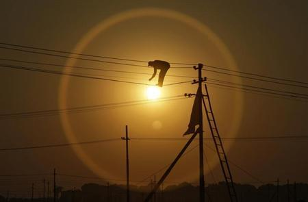 An employee from the electricity board works on newly installed overhead power cables ahead of the ''Kumbh Mela'' as the sun sets in Allahabad December 7, 2012. REUTERS/Jitendra Prakash/Files