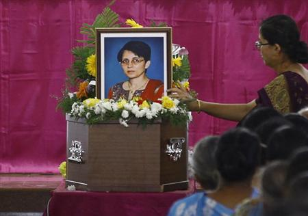 A woman puts flowers on Jacintha Saldanha's coffin during her funeral inside a church in Shirva, about 52 km (32 miles) north of Mangalore December 17, 2012. REUTERS/Stringer/Files