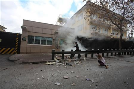 A security officer runs after an explosion at the entrance of the U.S. embassy in Ankara February 1, 2013. REUTERS/Yavuz Ozden/Milliyet Daily Newspaper