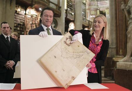 Former U.S. governor of California Arnold Schwarzenegger (L) looks on as director of the Austrian National Library (Oesterreichische Nationalbibliothek) Johanna Rachinger adjusts a historic map of California from 1666, in the State Hall of the Austrian National Library in the historic Hofburg palace in Vienna January 31, 2013. REUTERS/Herwig Prammer