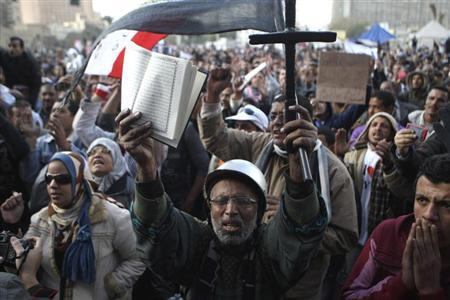 A man holds a cross and the Koran at Tahrir Square in Cairo February 1, 2013. REUTERS/Mohamed Abd El Ghany