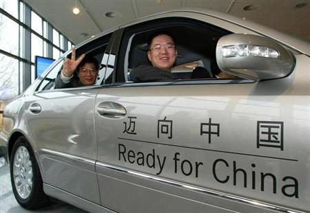 Gary Yu, employee at the Beijing Automotive Industry Holding Company Ltd. and Tong Zhi Yuan (L), Executive Vice Preident of Beijing Jeep Corporations Ltd., sit in a Mercedes Benz limousine ahaed of a joint venture signing ceremony at a Mercedes Benz plant in Bremen November 26, 2004. REUTERS/Christian Charisius