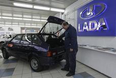 Мужчина рассматривает автомобиль Lada в дилерском центре в Санкт-Петербурге 27 ноября 2012 года. Крупнейший российский автопроизводитель Автоваз увеличил объем продаж автомобилей Lada в РФ на 3,5 процента до 30.037 штук, сообщила компания в пятницу. REUTERS/Alexander Demianchuk