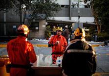 """Al menos 32 personas murieron y 121 resultaron heridas en una explosión en los edificios centrales de la petrolera mexicana Pemex, una de las mayores productoras de crudo del mundo, informó el viernes el director general de la compañía, Emilio Lozoya, un día después de la tragedia. En la imagen, trabajadores de rescate del equipo conocido como """"Topos"""" se toman un descanso frente a la sede de la petrolera estatal Pemex en Ciudad de México, el 1 de febrero de 2013. REUTERS/Bernardo Montoya"""