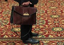 La creación de empleo de Estados Unidos se aceleró modestamente en enero y los incrementos de los dos meses anteriores fueron mayores de lo que se había informado inicialmente, respaldando la opinión de que la lenta recuperación de la economía está en curso pese a una inesperada contracción de la actividad en el último trimestre de 2012. En la imagen de archivo, un hombre sostiene su maletín mientras espera en una cola durante una feria de empleo en Melville, Nueva York, en julio del año pasado. REUTERS/Shannon Stapleton