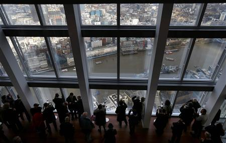 Visitors look out from windows in The View gallery at the Shard, western Europe's tallest building, in London February 1, 2013. REUTERS/Andrew Winning