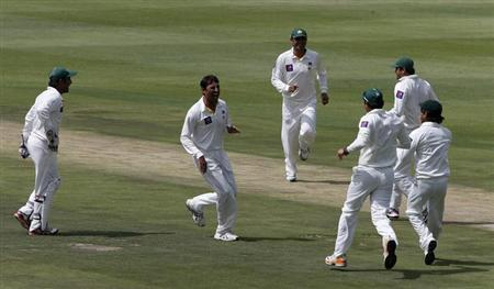 Pakistan's Younis Khan (C) celebrates with teammates after taking the wicket of South Africa's Hashim Amla during the first day of their first test cricket match in Johannesburg, February 1, 2013. REUTERS/Mike Hutchings